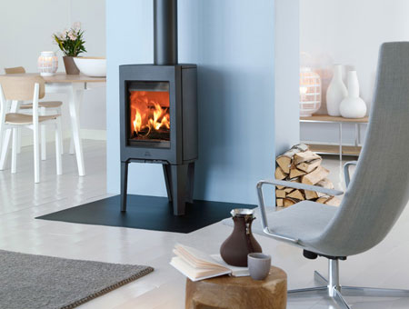 Jotul F 162 wood burning stove in room with log pile at side